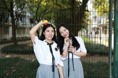 Il sorriso cinese della studentessa della High School dell'Asia di bellezza adorabile di Bestie gode del tempo libero sulla cola  Fotografie Stock