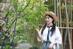 Il sorriso cinese della studentessa della High School dell'Asia di bellezza adorabile gode del gioco di tempo libero nel bambù de Immagine Stock