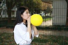 Il sorriso cinese della studentessa della High School dell'Asia di bellezza adorabile gode del tempo libero sul pallone di giallo Fotografia Stock Libera da Diritti