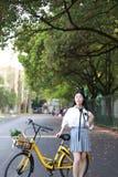 Il sorriso cinese della studentessa della High School dell'Asia di bellezza adorabile gode del tempo libero sulla bici di giro de Fotografie Stock Libere da Diritti