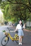 Il sorriso cinese della studentessa della High School dell'Asia di bellezza adorabile gode del tempo libero sulla bici di giro de Immagini Stock