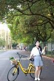 Il sorriso cinese della studentessa della High School dell'Asia di bellezza adorabile gode del tempo libero sulla bici di giro de Fotografia Stock Libera da Diritti