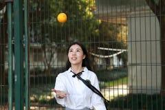 Il sorriso cinese della studentessa della High School dell'Asia di bellezza adorabile gode del tempo libero sulla cola dell'aranc Fotografie Stock Libere da Diritti