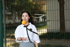 Il sorriso cinese della studentessa della High School dell'Asia di bellezza adorabile gode del tempo libero sulla cola dell'aranc Fotografie Stock