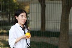 Il sorriso cinese della studentessa della High School dell'Asia di bellezza adorabile gode del tempo libero sulla cola dell'aranc Fotografia Stock Libera da Diritti