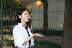 Il sorriso cinese della studentessa della High School dell'Asia di bellezza adorabile gode del tempo libero sulla cola dell'aranc Immagine Stock Libera da Diritti