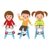 Il sorriso dei bambini sta sedendosi in una sedia Fotografia Stock