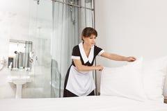 Il sorriso del cliente mi incita a ritenere meglio Femmina nel letto di fabbricazione uniforme della domestica in camera da letto fotografia stock