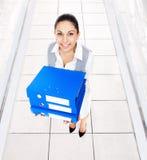 Il sorriso della donna di affari, tiene la cartella blu della pila fotografia stock