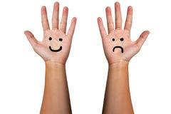 Il sorriso e l'aggrottare le sopracciglia della mano fotografia stock