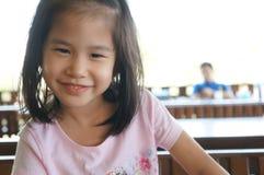 Il sorriso felice della ragazza asiatica si siede la sedia fotografia stock