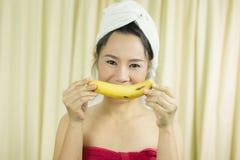 Il sorriso sostituto della banana della tenuta della donna, triste, divertente, porta una gonna per coprire il suo seno dopo i ca fotografie stock