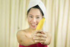 Il sorriso sostituto della banana della tenuta della donna, triste, divertente, porta una gonna per coprire il suo seno dopo i ca immagine stock libera da diritti