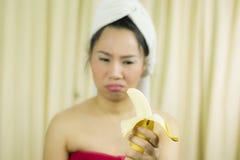 Il sorriso sostituto della banana della tenuta della donna, triste, divertente, porta una gonna per coprire il suo seno dopo i ca fotografie stock libere da diritti