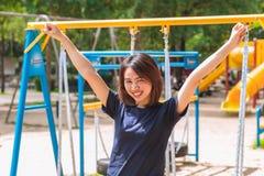 Il sorriso teenager asiatico nel parco aumenta su mano due Fotografia Stock Libera da Diritti