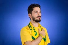 Il sostenitore brasiliano della squadra nazionale di calcio sta ascoltando immagine stock libera da diritti