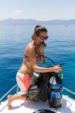 Il subaqueo femminile sta controllando la sua attrezzatura immagine stock libera da diritti