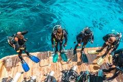 Il subaqueo si siede sull'yacht e aspetta per tuffarsi immagine stock libera da diritti