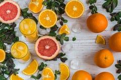 Il succo d'arancia con ghiaccio in vetri si avvicina all'agrume ed alla menta a fondo di legno leggero Fotografie Stock