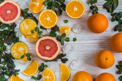Il succo d'arancia con ghiaccio in vetri si avvicina all'agrume ed alla menta a fondo di legno leggero Fotografia Stock Libera da Diritti