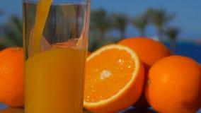 Il succo d'arancia del primo piano ha versato in un vetro archivi video