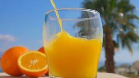 Il succo d'arancia del primo piano ha versato in un vetro stock footage
