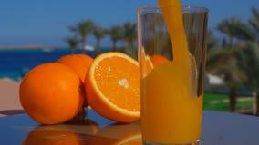 Il succo d'arancia fresco del primo piano ha versato in un vetro stock footage