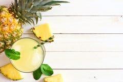 Il succo di ananas, la vista superiore, lato rasenta il legno bianco immagine stock