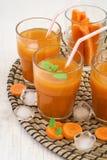 Il succo di carota fresco con polpa con ghiaccio e la menta coprono di foglie Fotografie Stock
