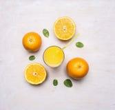 Il succo di recente schiacciato dalle arance in un vetro con una paglia, diffusione fuori intorno alle arance mint il fondo rusti Fotografia Stock