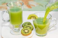 Il succo fresco del kiwi ha versato in una tazza dalla bottiglia Fuoco selettivo Immagine Stock