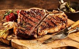 Il succulente ha grigliato la bistecca di bistecca con l'osso con la forcella ed il coltello Immagine Stock Libera da Diritti