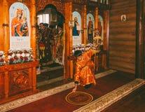 Il suddiacono del giovane raddrizza la coperta davanti all'altare in una chiesa ortodossa alla liturgia divina Immagini Stock