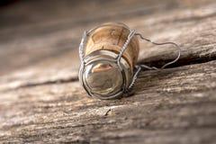 Il sughero di Champagne con il cappuccio allegato del metallo e del cavo che si trova su vecchio corteggia Immagine Stock