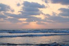 Il Sun dietro si rannuvola l'oceano infinito - carta da parati naturale del tramonto Immagini Stock