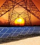 Il Sun ha messo con la struttura della torre ad alta tensione di energia elettrica e Fotografie Stock Libere da Diritti
