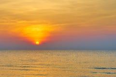 Il Sun ha messo sul mare dell'acqua con le onde ed il fondo arancio del cielo di colore Immagini Stock Libere da Diritti