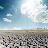 Il Sun più si rannuvola la terra di siccità Fotografia Stock