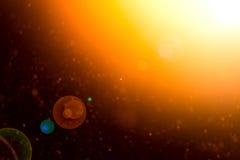 Il sunflare dorato giallo con la stella gradisce le forme astratte su un fondo nero - Fotografia Stock