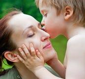 il suo figlio baciante della madre Fotografie Stock Libere da Diritti