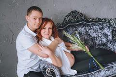 Il suo marito che abbraccia donna incinta sul sofà grigio con lavanda a disposizione Fotografia Stock Libera da Diritti
