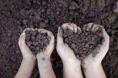 Il suolo della tenuta della mano del bambino e del genitore nel cuore modella per piantare immagine stock libera da diritti