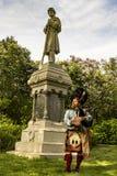 Il suonatore di cornamusa scozzese si è vestito in vestito rosso e nero tradizionale dal tartan Immagine Stock