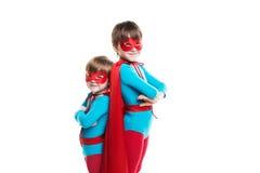 Il supereroe dei bambini con una maschera ed il mantello esaminano la macchina fotografica isolata fotografia stock libera da diritti