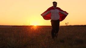 Il superman in un impermeabile rosso vola nei raggi del tramonto al suoi sogno e risate Uomo d'affari Hero comics video d archivio