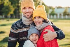 Il supporto adorabile del piccolo bambino vicino ai suoi genitori affettuosi, gode di di spendere il tempo insieme, si abbraccia, immagine stock libera da diritti