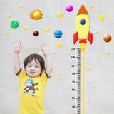 Il supporto asiatico felice del bambino del primo piano per altezza della misura con il fumetto sveglio alla parete di pietra di  fotografia stock