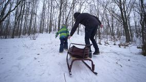 Il supporto del genitore, il padre aiuta la montagna nevosa di salita del figlio con le slitte in mani all'inverno video d archivio