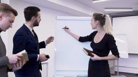 Il supporto della donna di affari sullo strato bianco seleziona il grafico, che i colleghi esaminano per lo studio archivi video