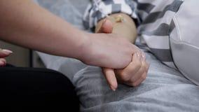 Il supporto delle donne si tiene per mano con il catetere sulla terapia nel reparto della clinica, primo piano delle mani archivi video
